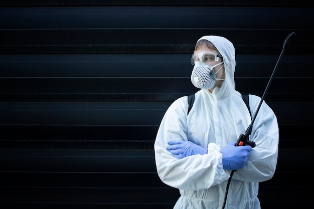 Portrait of professional exterminator holding sprayer with chemicals for pest control