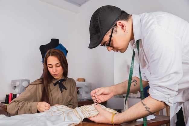 Portrait of a professional fashion designer sewing a dress with his assistant in the workshop.