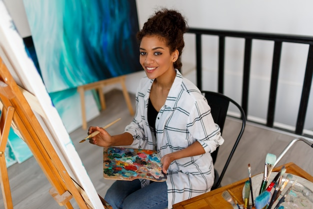 Portrait of professional female artist painting on canvas in studio. woman painter at her  workspace.