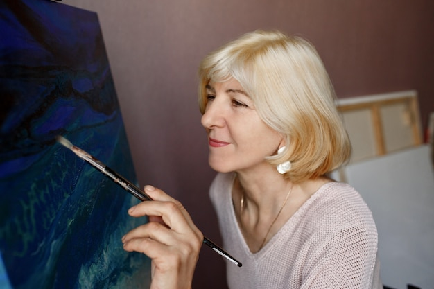Portrait of professional female artist painting on canvas