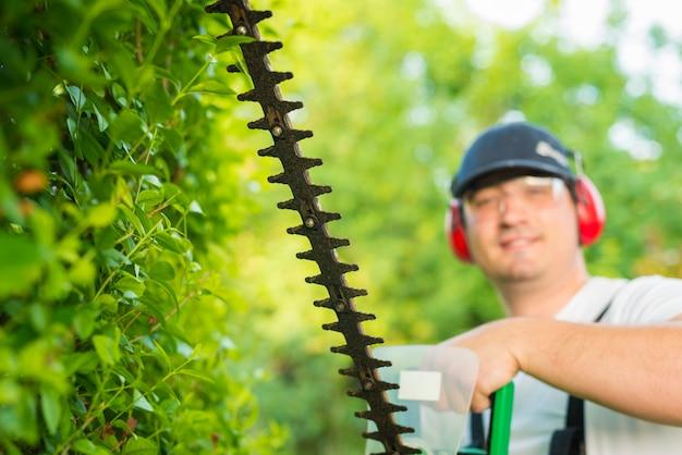 Ritratto del giardiniere professionista che tiene il trimmer in cortile
