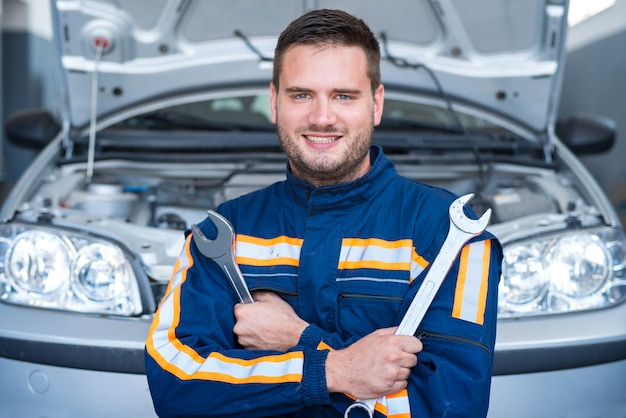 Portrait of professional handsome car mechanic holding wrenches in front of the automobile with opened hood