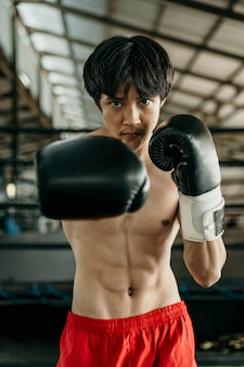Portrait of professional male boxer make a hitting motion against boxing training ground