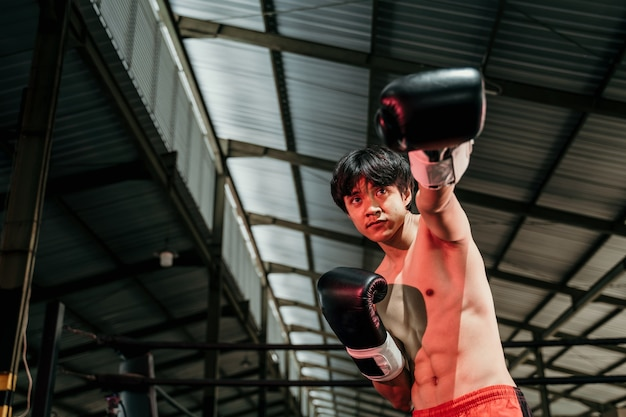 Portrait of professional male boxer make a hitting motion with the copyspace beside it at boxing training ground