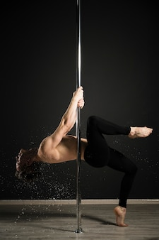 Portrait of professional male model performing a pole dance