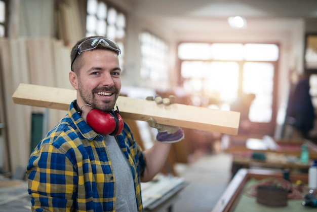 Portrait of professional middle aged carpenter with wood plank and tools standing in his woodworking workshop