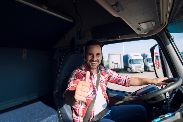 Portrait of professional motivated truck driver holding thumbs up in truck cabin