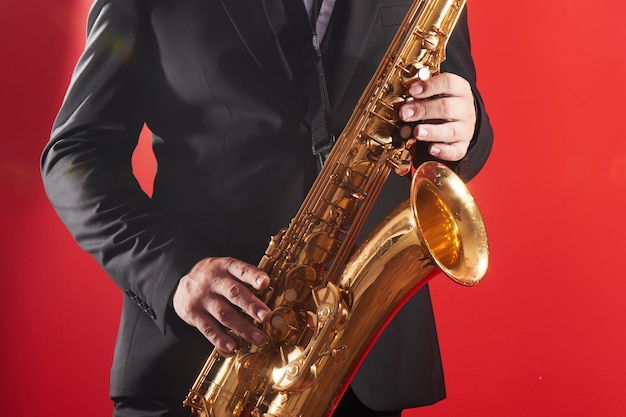 Portrait of professional musician saxophonist man in  suit plays jazz music on saxophone, red background