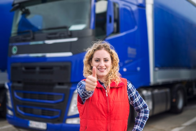 Portrait of professional truck driver showing thumbs up and smiling