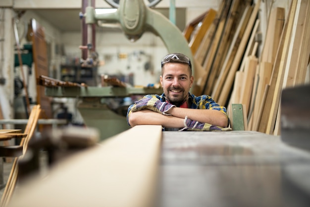 Portrait of professional woodworker standing next to a machine and wood material in his carpentry workshop