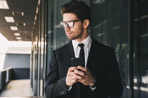 Portrait of professional young businessman dressed in formal suit standing outside glass building, and holding smartphone