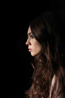 Portrait in profile of beautiful sad girl with long curly hair looking straight in darkness