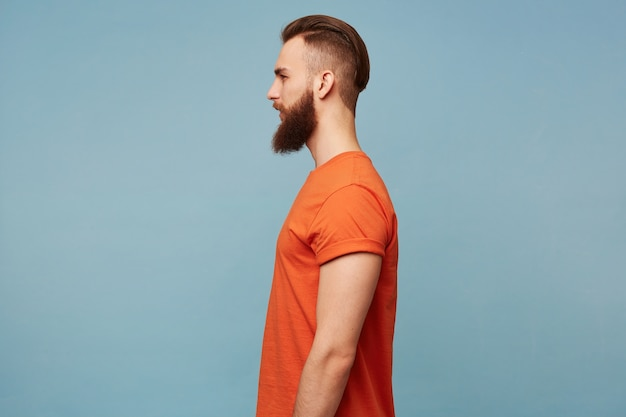 Portrait in profile of a guy with a fashionable hairstyle and a shaven head and a long thick beard in a red t-shirt standing sideways isolated on a blue