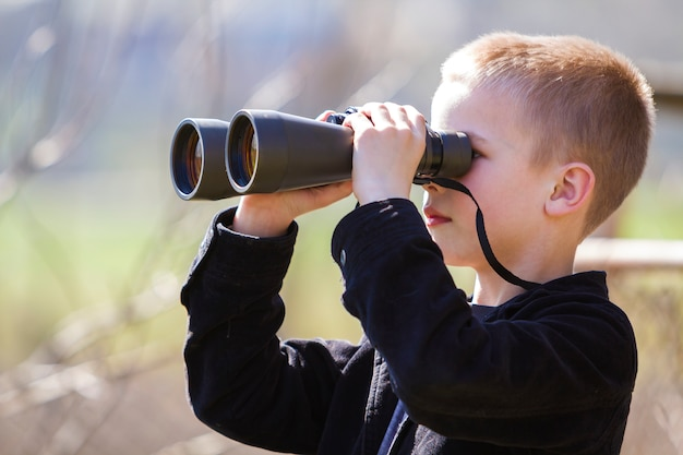 Portrait in profile of little handsome cute blond boy looking thoughtfully through binoculars