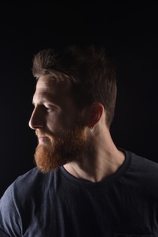 Portrait of profile of a serious man on black