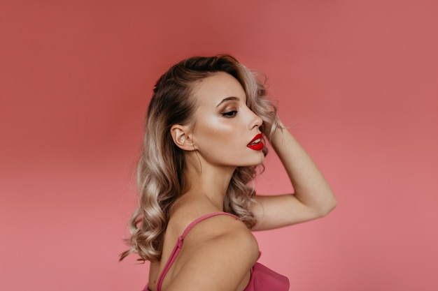 Portrait in profile in studio of beautiful young blonde with curly hair and brightly painted pink lips, posing for camera showing her tender feminine shoulders