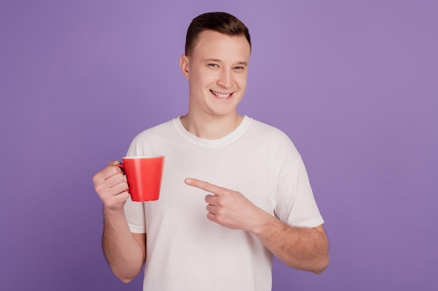 Portrait of promoter man hold coffee cup direct finger gesture on purple background