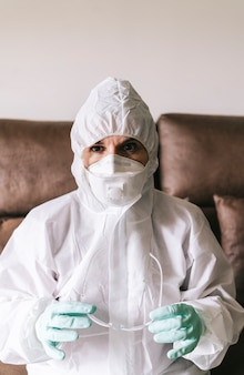 Portrait of protected woman with safety suit, glasses and mask before a pandemic or virus