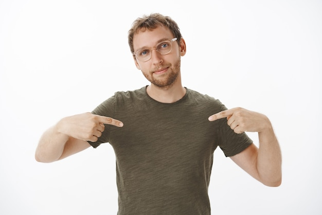 Portrait of proud and pleased self-assured handsome male entrepreneur in glasses and dark-green t-shirt pointing at himself and smiling bragging about own achievements