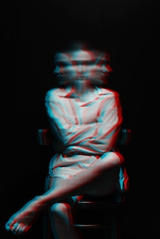 Portrait of a psych girl with schizophrenia and mental disorders in a white shirt on a black background. black and white with 3d glitch virtual reality effect