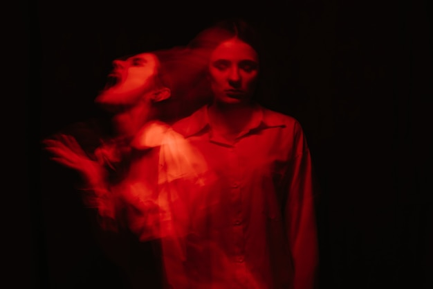 Portrait of a psychotic woman with schizophrenic diseases and mental disorders with a blurry on a black background