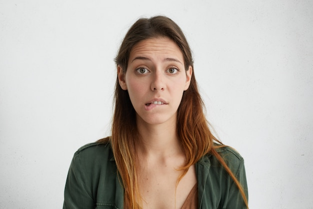 Portrait of puzzled woman with long face and straight dyed hair wearing green jacket looking with big opened eyes biting her lower lip having some doubts and uncertainty
