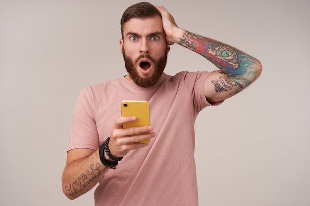 Portrait of puzzled young bearded male with short haircut holding mobile phone in hand and looking surprisedly, reading unexpected news, standing on white