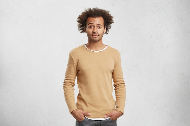 Portrait of puzzled young dark skined afro american male wears fashionable clothes, keeps hands in pockets