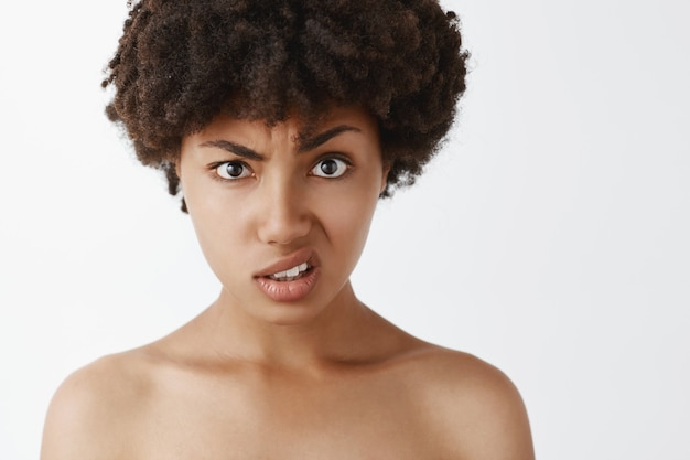 Portrait of questioned and clueless intense african american woman with afro hairstyle, raising eyebrow and upper lip, being confused with stupid person