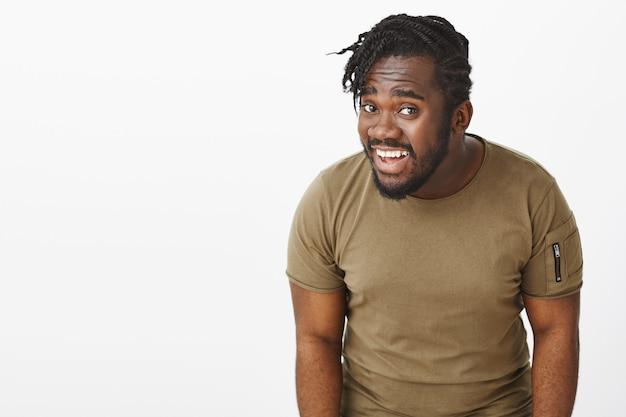 Ritratto di ragazzo interrogato in una maglietta marrone in posa contro il muro bianco