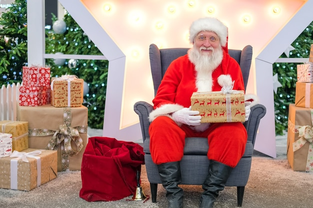 Portrait real authentic santa claus with christmas gifts in hands sitting in shopping mall.