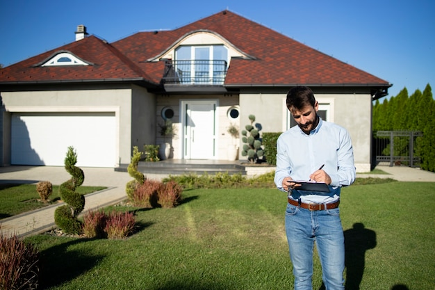 Portrait of real estate agent checking the contract before customers arrive to buy the house