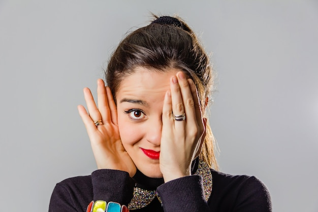 Portrait of real young girl with red lips covering one of her eyes with a hand over gray background