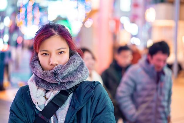 Portrait of red hair asian woman is walking in busy street of sendai japan