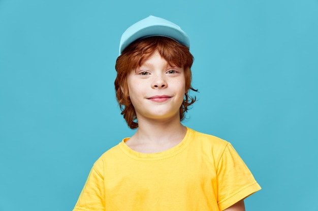 Portrait of red-haired boy cropped view blue background fashionable clothes childhood