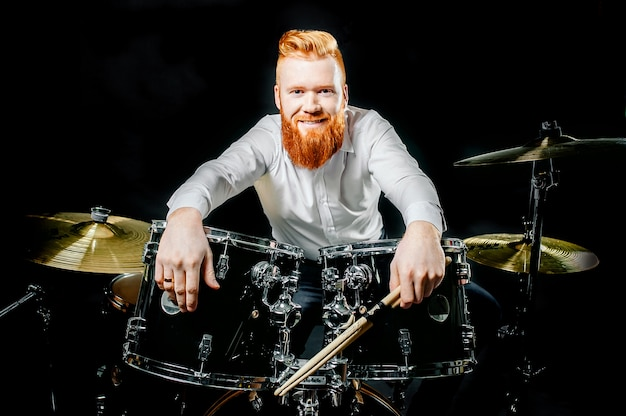 Portrait of a red-haired emotional man playing drums and cymbals and holding a stick.