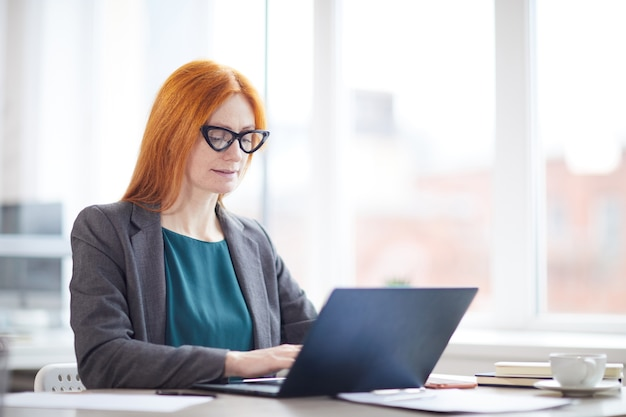 Portrait of red haired female boss using laptop while sitting against window in office