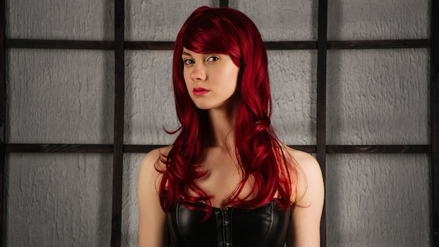 Portrait of red-haired girl in a leather corset - image