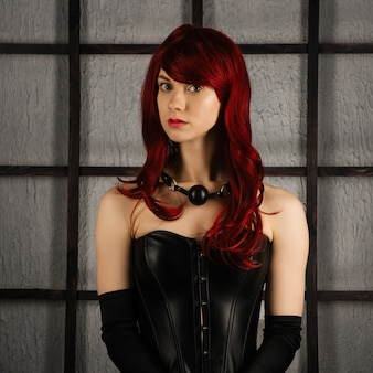 Portrait of red-haired girl in a leather corset with gag ball. bdsm outfit