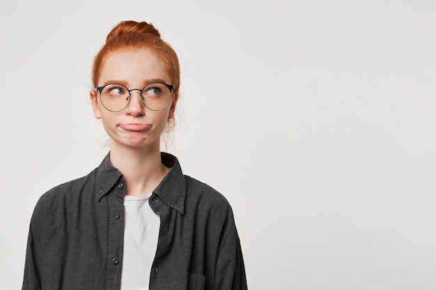 Portrait of a red-haired girl looks away wearing a men's black shirt