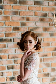 Portrait of red haired girl wearing wedding dress against a white studio.