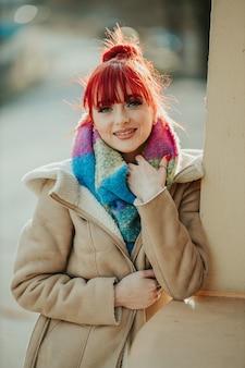 Ritratto di una ragazza dai capelli rossi con la frangia che tiene la sua sciarpa colorata