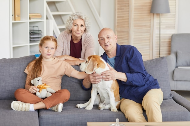 Portrait of red haired girl with grandparents sitting on couch and playing with dog in cozy home