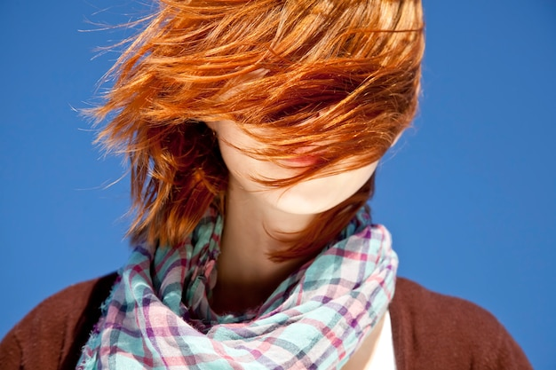 Portrait of red-haired girl with scarf on blue background.