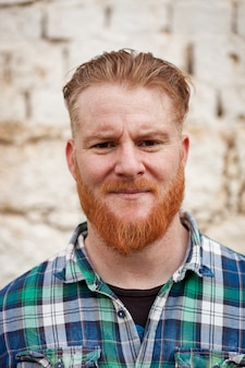 Portrait of red haired hipster man looking at camera