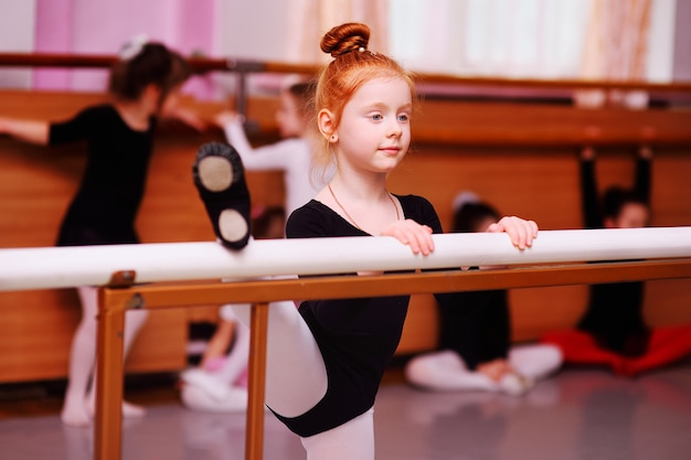 Portrait of a red-haired little girl ballerina at the ballet barre