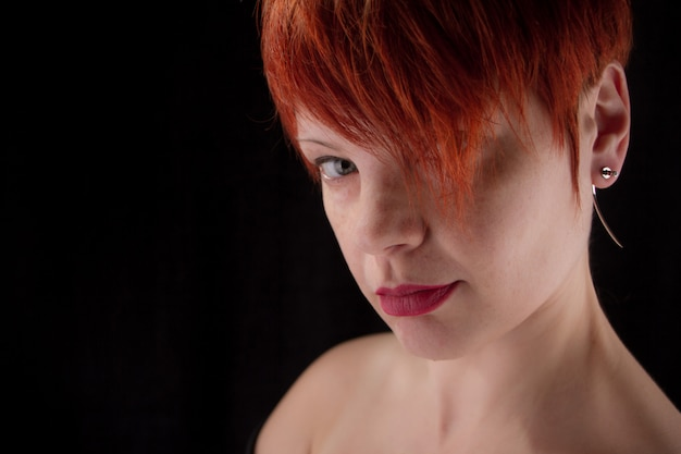 Portrait of a red haired middle aged woman with bare shoulders on a black background