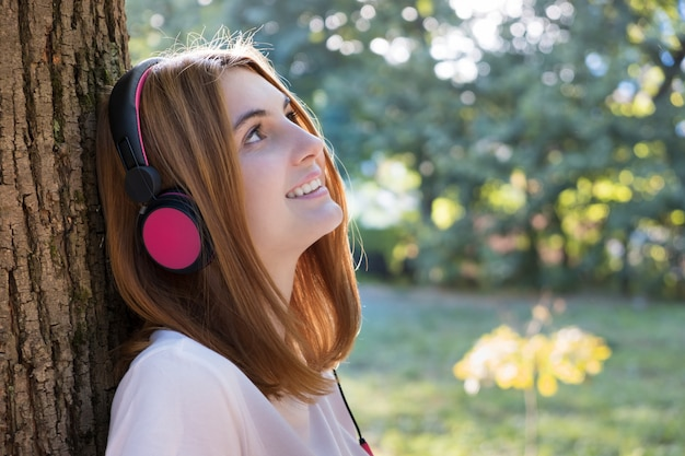 Portrait of red haired teenage girl listening to music in big pink earphones outdoors leaning to a tree.
