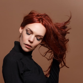 Portrait of a red-haired woman on a beige background.