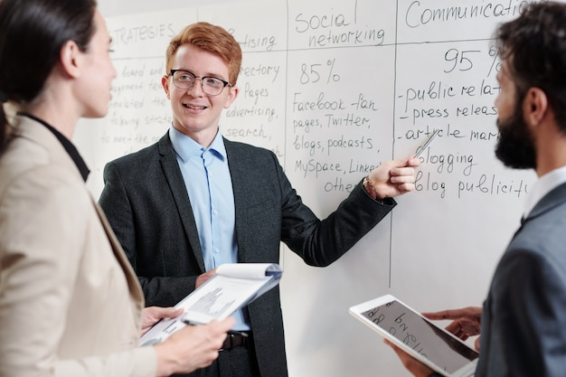 Portrait of red haired young businessman standing by whiteboard and pointing at plans while discussing startup project with team